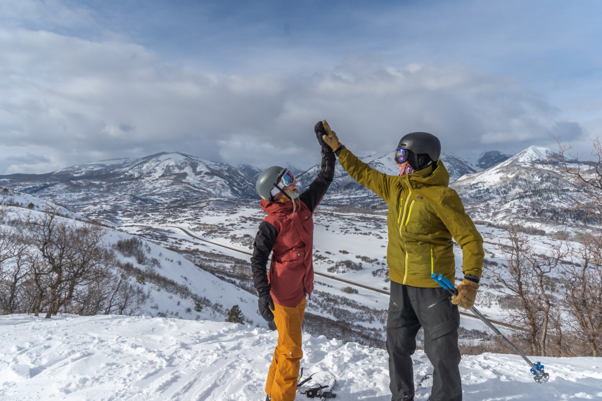 Young man and woman high fiving at top of mountain