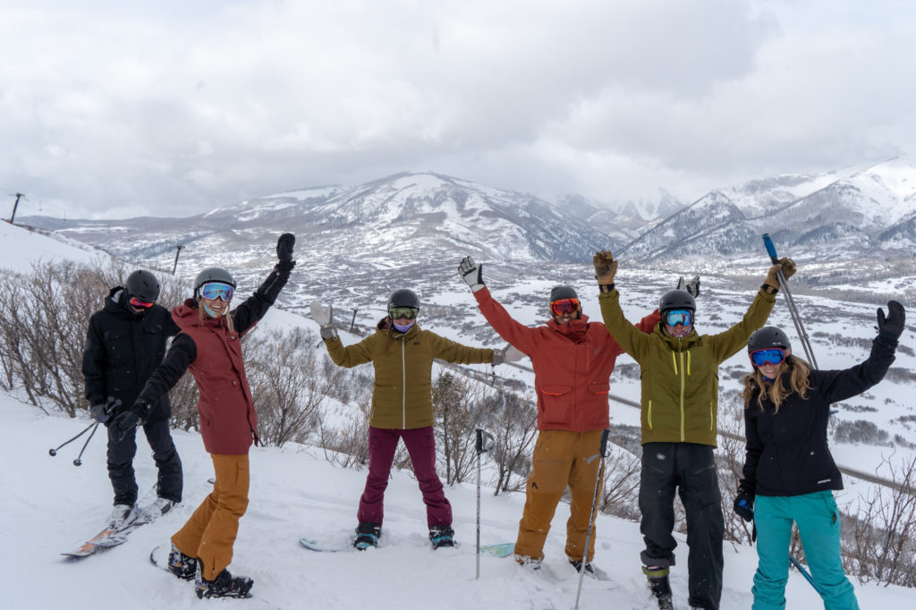 Group of young adults waving at top of mountain